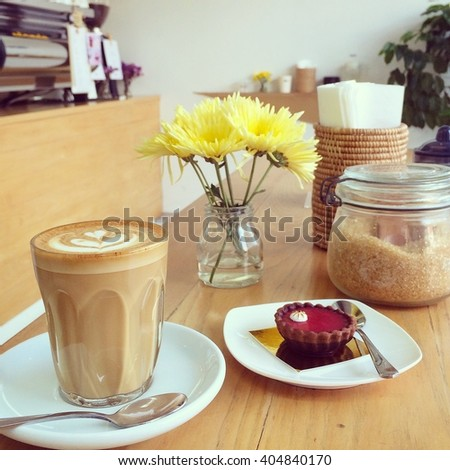 latte and raspberry cheese tart at the cafe in soft tone vintage filter effect - stock photo