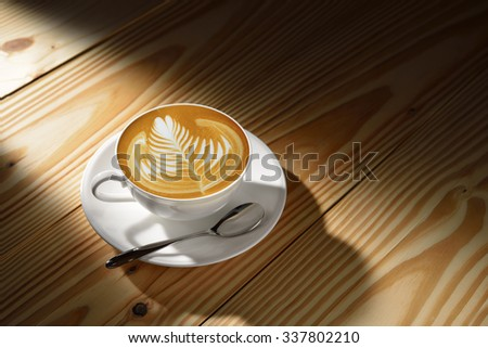 Latte Art, a cup of cafe latte in the morning light on wooden background - stock photo