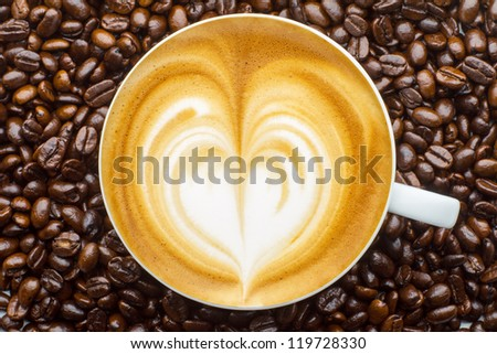 Latte art, coffee in coffee beans background - stock photo