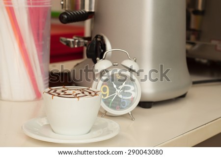 Latte art coffee in white cup and clock on coffee counter