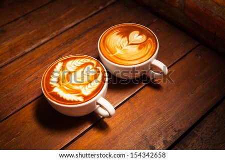 Latte art,Cup of coffee on the wooden desk. - stock photo