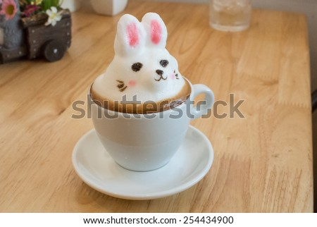 Latte Art 3D. Made by milk foam top on the cup of hot coffee or hot chocolate. build it to thing that customer love. place on the wood table - stock photo