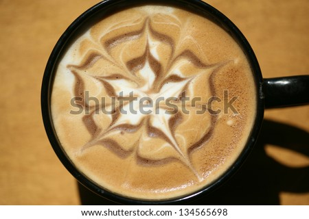 Latte Art, Designs drawn with steamed milk in hot fresh rich coffee in a ceramic coffee cup. - stock photo