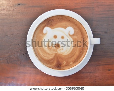 "Latte Coffee art ""Dog Face"" on the wooden desk. - stock photo"