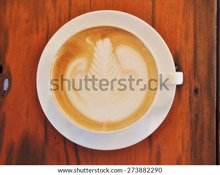 "Latte Coffee art ""Rosetta"" on the wooden desk. - stock photo"