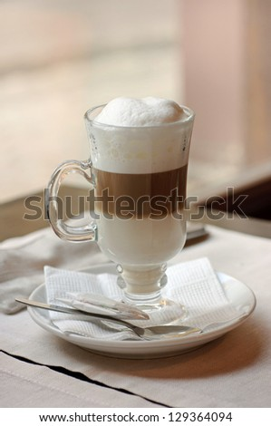 Latte coffee cocktail in a cafe with spoon and napkin - stock photo