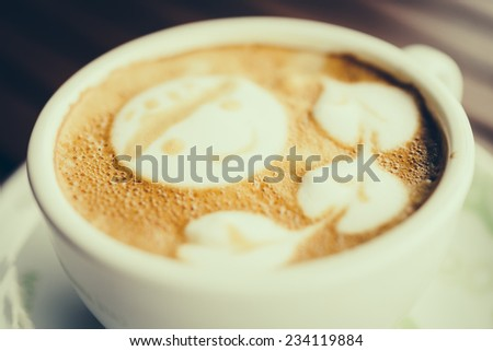 Latte coffee cup on wooden table - vintage effect style pictures - stock photo