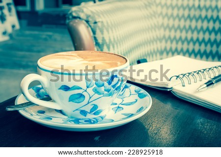 Latte coffee cup with notebook and pen, vintage green tone  - stock photo