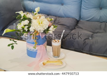 Latte in a glass and fresh eclair on dessert dish, bouquet of flowers on the background. Blank white chocolate plate on the eclair where text can be.