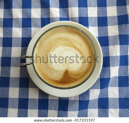 Latte in Italy on a blue checkered table  cloth