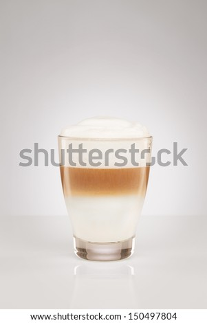 latte macchiato in a small glass on gray background