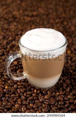 Latte Macchiato on a lot of coffee beans - stock photo