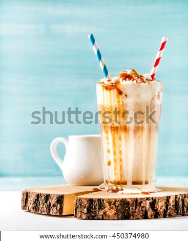 Latte macchiato with whipped cream and caramel sauce in tall glass with two straws on wooden board over blue painted wall background, selective focus, copy space, vertical composition - stock photo