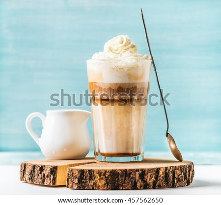 Latte macchiato with whipped cream, serving silver spoon and pitcher on wooden round board over blue painted wall background, selective focus, horizontal composition - stock photo