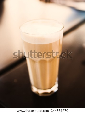 Latte on a cafe table, shallow dof - stock photo