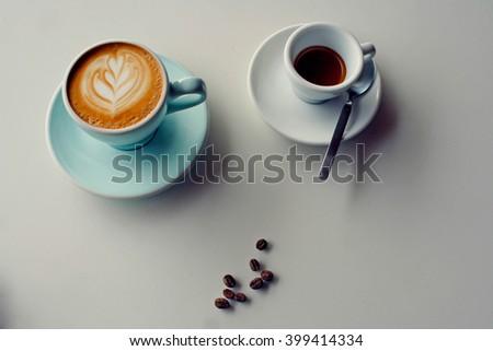 latte or cappuccino coffee and espresso shot on marble white desk in retro filter - stock photo