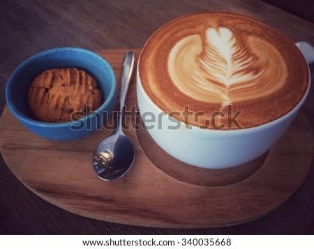 latte or cappuccino coffee in dark tone retro film filter effect - stock photo