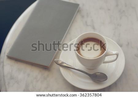 latte or cappuccino or espresso machiato coffee with notebook on marble desk in soft tone pastel retro filter effect - stock photo