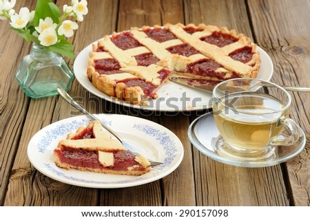 Lattice cake with strawberry jam cut, piece of cake, bunch of jasmine and green tea  - stock photo