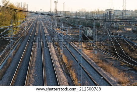 Lattice train tracks in cargo area at sunset   - stock photo
