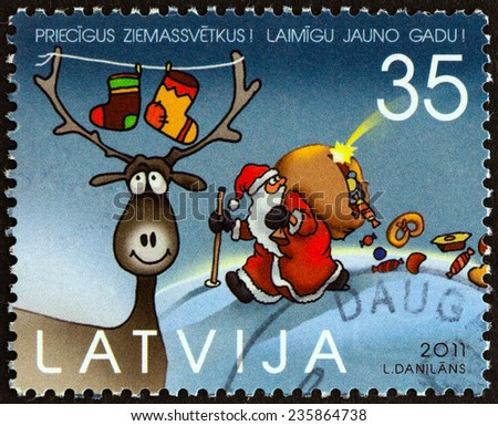 """LATVIA - CIRCA 2011: A stamp printed in Latvia from the """"Christmas """" issue shows Deer and Santa Claus, circa 2011.  - stock photo"""