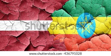Latvia flag with Ethiopia flag on a grunge cracked wall - stock photo