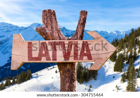 Latvia wooden sign with winter background - stock photo
