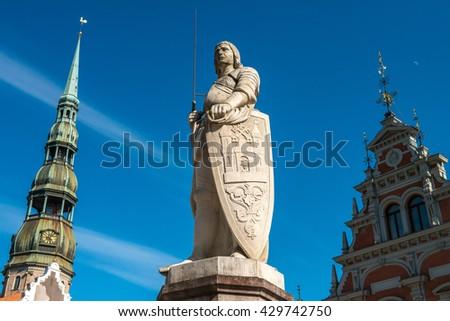 Latvian landmark - house of the Blackheads, sculpture of Saint Roland and Saint Peters Church in old city Riga, Latvia - stock photo