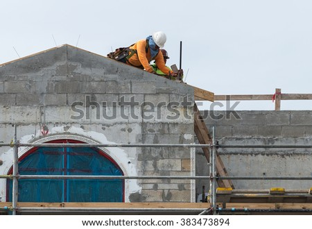 LAUDERDALE BY THE SEA, FL - JANUARY 13: Two unidentified workers are nailing board to the roof of a new building on January 18, 2016 in a beach town of Lauderdale By The Sea in Florida. - stock photo