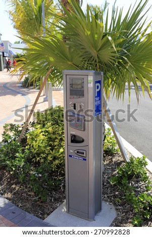 LAUDERDALE-BY-THE-SEA, FL, USA - APRIL 7, 2014: Closeup of an electric parking meter with signage in the shade of palm trees and plants of a newly redesigned parking lot.  - stock photo
