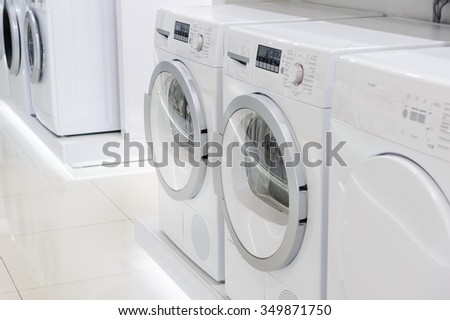 laudry dryers, washing machines and other domestic appliance equipment in the store - stock photo