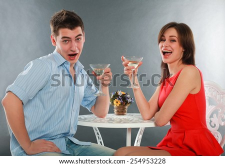 Laugh and drunk couple with glasses of champagne at table, in studio isolated on gray - stock photo