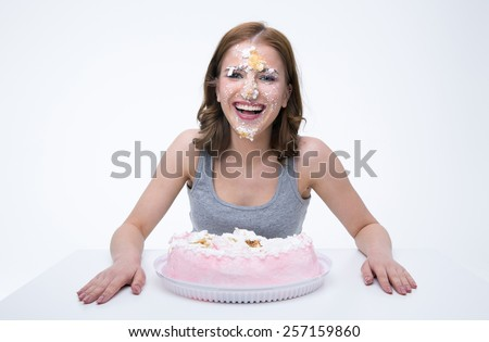 Laughign young woman sitting at the table with cake at her face - stock photo