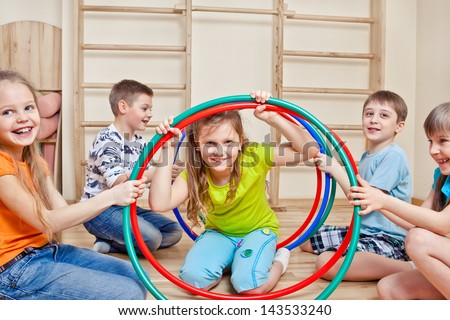 Laughing active children holding hula hoops - stock photo