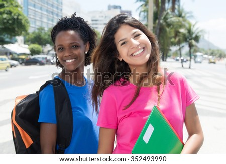 Laughing african american and caucasian student in city - stock photo