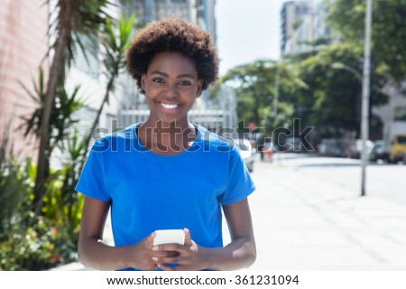 Laughing african american woman in a blue shirt typing message