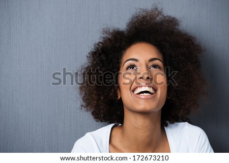 Laughing African American woman with an afro hairstyle and good sense of humor smiling as she tilts her head back to look into the air - stock photo