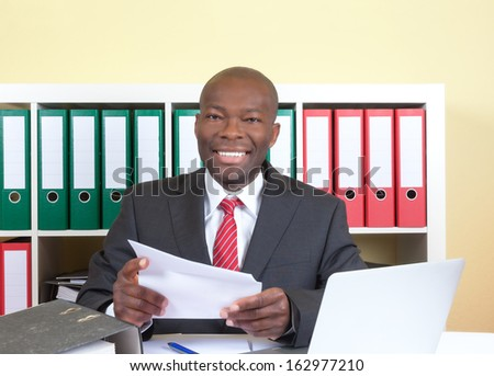 Laughing african businessman reading a letter  - stock photo