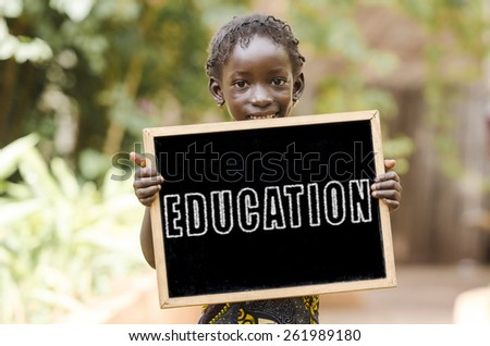Laughing African Girl with Education on a Chalkboard. Blackboard with written Education on is being hold by an African girl. - stock photo