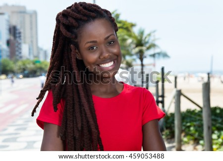 Laughing african woman with dreadlocks in the city