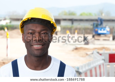 Laughing african worker at construction zone looking at camera  - stock photo