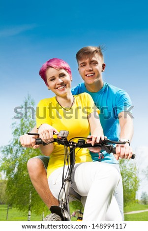 Laughing and smiling young couple sitting on the bike together