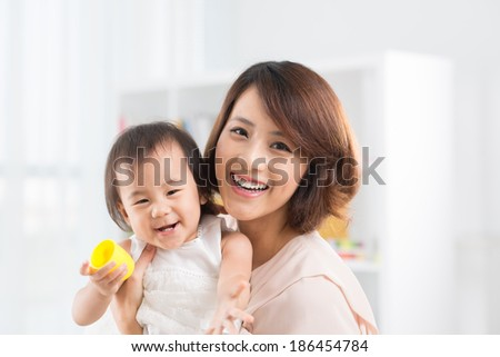 Laughing Asian mother and daughter looking at the camera - stock photo