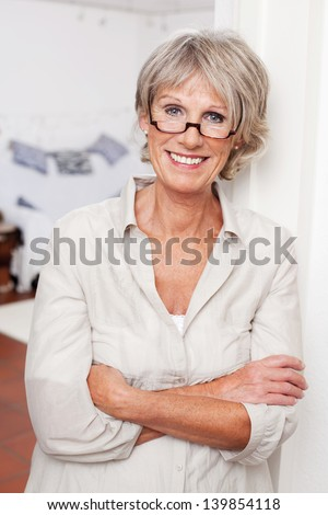 Laughing attractive senior woman wearing glasses standing with folded arms - stock photo