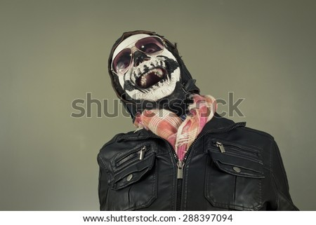 Laughing aviator with face painted as human skull - stock photo