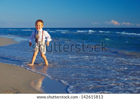 laughing baby boy having fun on the beach