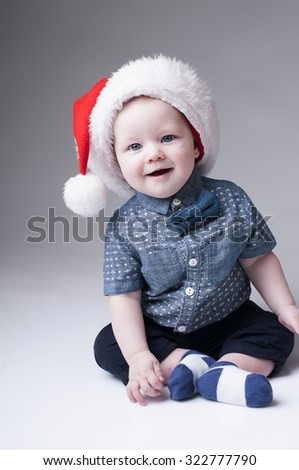 Laughing baby boy in santa hat cover gray background. - stock photo