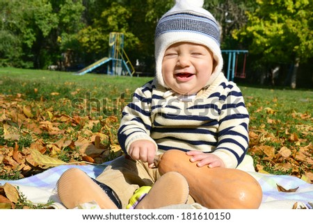 Laughing baby boy with pumpkin on a bright autumn leaves - stock photo
