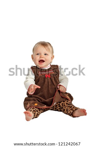 Laughing baby girl sits up. She has blue eyes, wispy hair, bare feet, and wears a brown velvet embroidered jumper with leopard print pants. Isolated/cut out on white background, vertical, copy space.