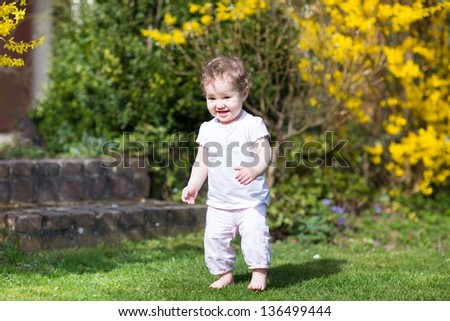 Laughing baby girl walking in the garden
